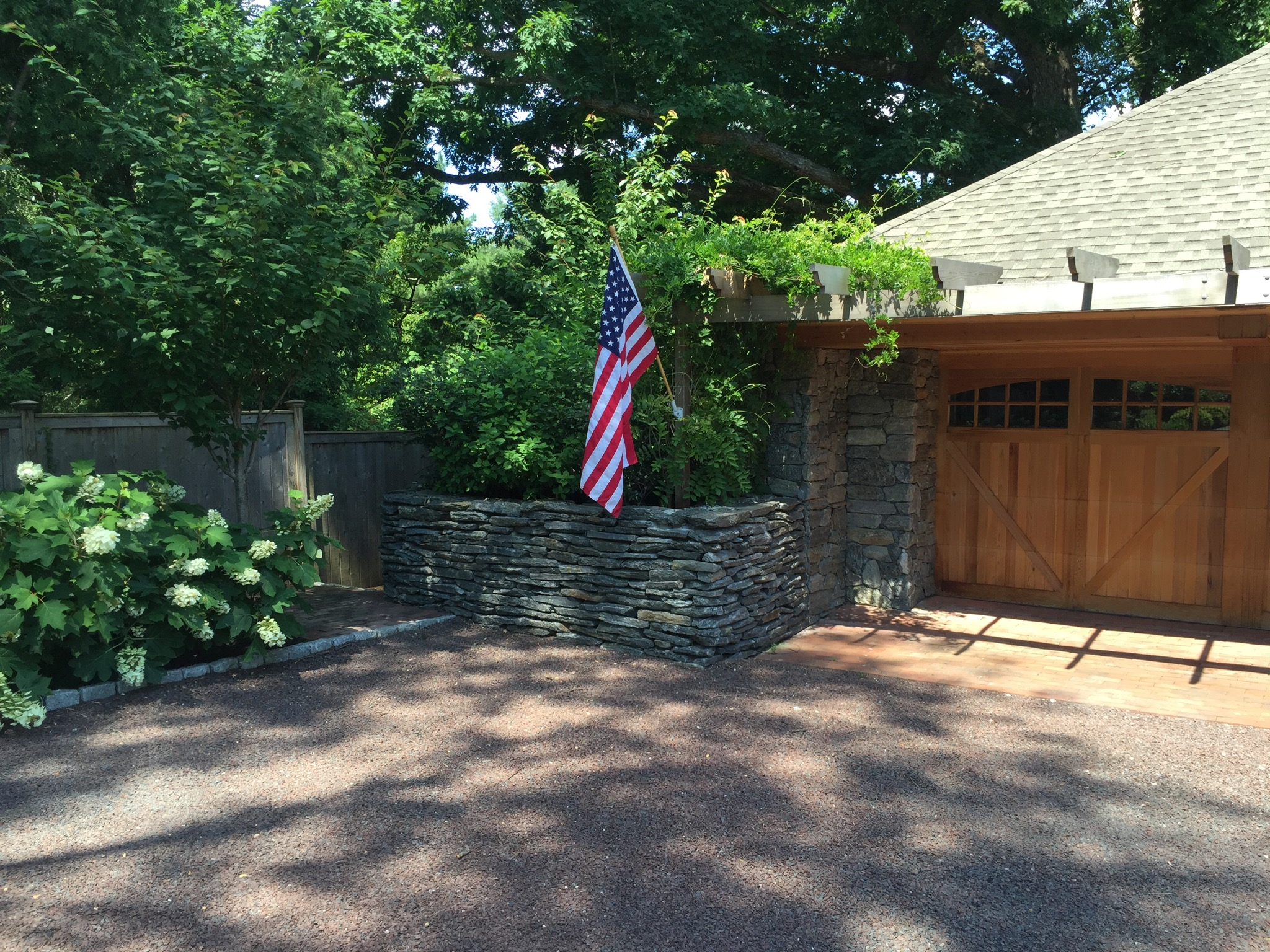 Cedar garage door and pergola, Wissahickon Schist wall & cobblestone edging